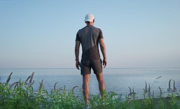 Um jovem fica em uma colina à beira-mar. vista traseira.
