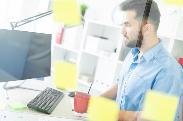 Um jovem fica no escritório perto de uma placa transparente com adesivos.