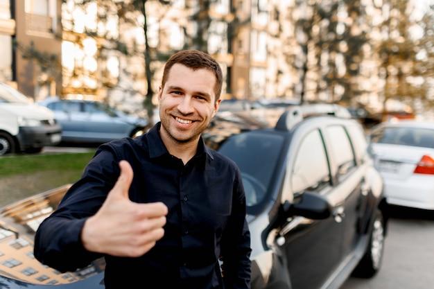 Um jovem fica perto de um carro e aparece um polegar. motorista de táxi olha para a câmera e sorri. ambiente urbano e tráfego