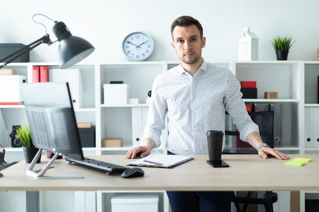 Um jovem fica perto de uma mesa no escritório