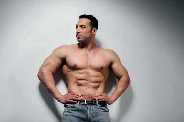 Um jovem fisiculturista atleta posa no estúdio em topless em jeans perto da parede. esporte.