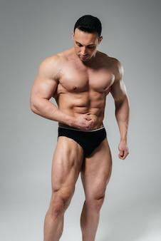 Um jovem fisiculturista atleta posa no estúdio em topless, exibindo seu abdômen e músculos. esporte.