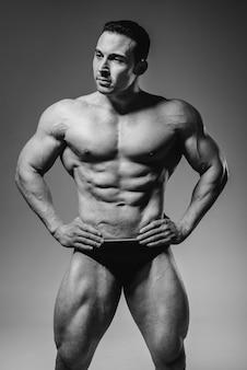 Um jovem fisiculturista atleta posa no estúdio em topless, exibindo seu abdômen e músculos. preto e branco.