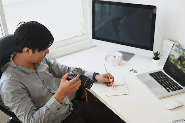 Um jovem fotógrafo revisando fotos em sua câmera e sentado em sua mesa