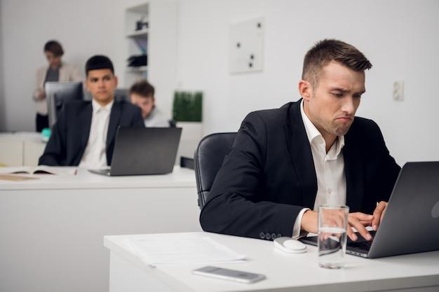 Um jovem funcionário de uma organização de crédito está chateado com as perdas e um mau negócio. sentado no local de trabalho em um laptop.