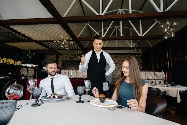Um jovem garçom com um avental estiloso serve uma mesa com um lindo casal em um restaurante requintado. atendimento ao cliente.