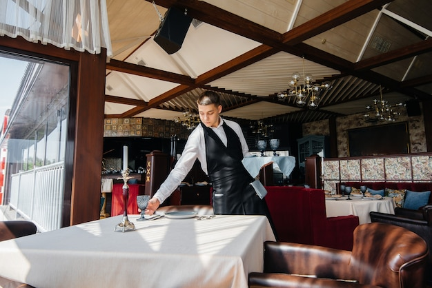 Um jovem garçom em um elegante uniforme está ocupado servindo a mesa em um belo restaurante gourmet. atividade de restaurante, de alto nível.