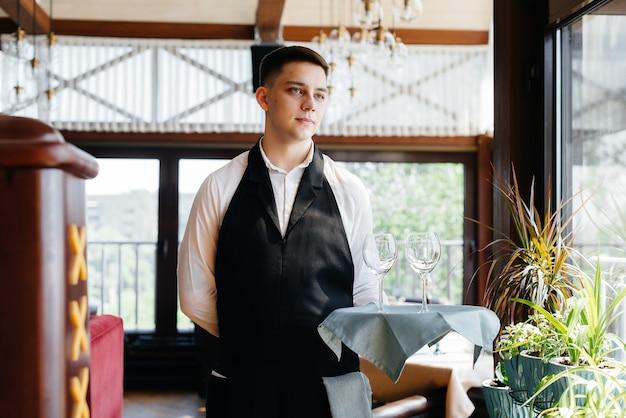 Um jovem garçom em um uniforme elegante está com copos em uma bandeja perto da mesa em um close-up de um belo restaurante gourmet. atividade de restaurante, de alto nível.