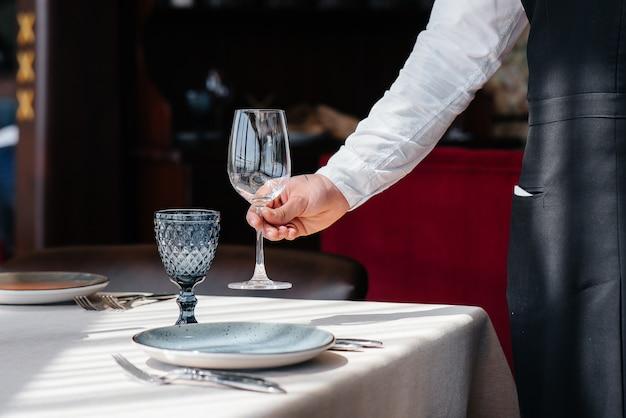Um jovem garçom em um uniforme elegante está ocupado servindo a mesa em um close-up de um belo restaurante gourmet. atividade de restaurante, de alto nível.