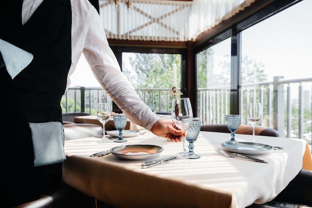 Um jovem garçom em um uniforme estiloso está empenhado em servir a mesa em um close-up de um belo restaurante gourmet. atividade de restaurante, de alto nível.