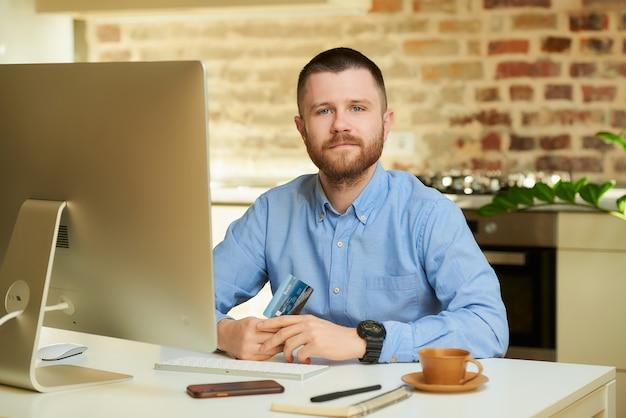 Um jovem gentil, com barba e camisa azul posando com seu cartão de crédito na frente do computador em casa