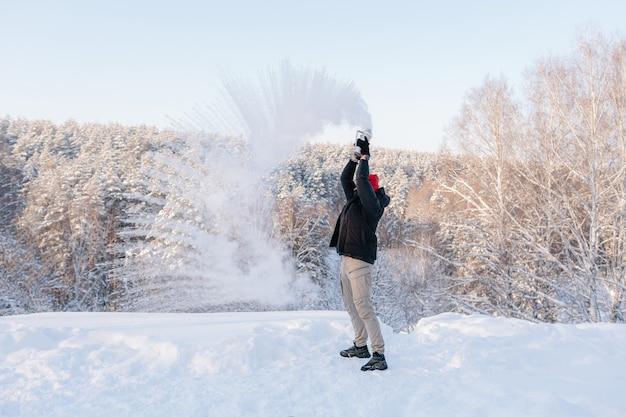 Um jovem gosta de um dia de inverno no fundo de uma floresta coberta de neve