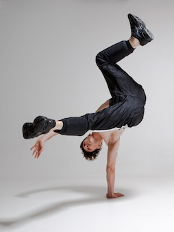 Um jovem gracioso está dançando um break dance no chão sem uma camiseta. truques complexos. corpo com tatuagens.