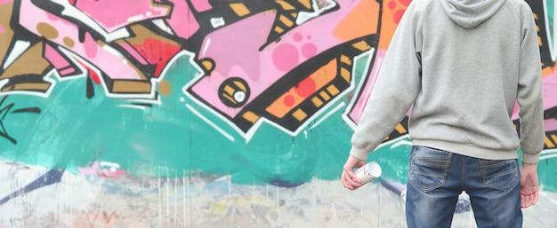 Um, jovem, graffiti, artista, em, um, cinzento, hoodie, olha, a, parede, com
