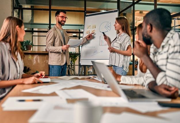 Um jovem grupo de empresários está discutindo um novo plano de negócios em um quadro negro, trabalhando em laptops enquanto está sentado em um escritório moderno.