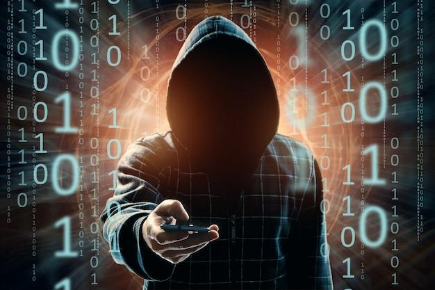 Um jovem hacker em um capô hackeia um smartphone, um ataque de hacker, uma silhueta de um homem, mídia mista