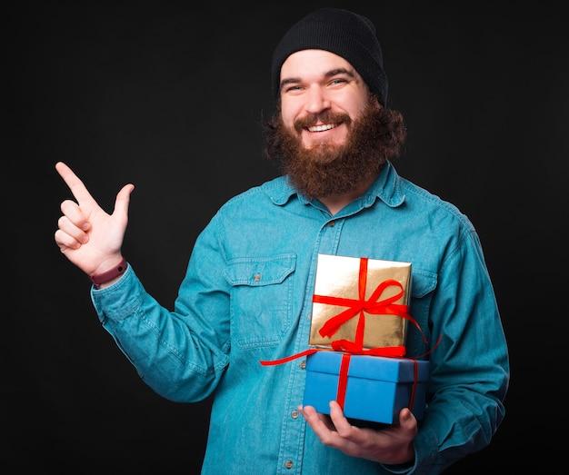 Um jovem hippie barbudo alegre segurando alguns presentes e olhando para a câmera sorrindo e apontando para outro lado