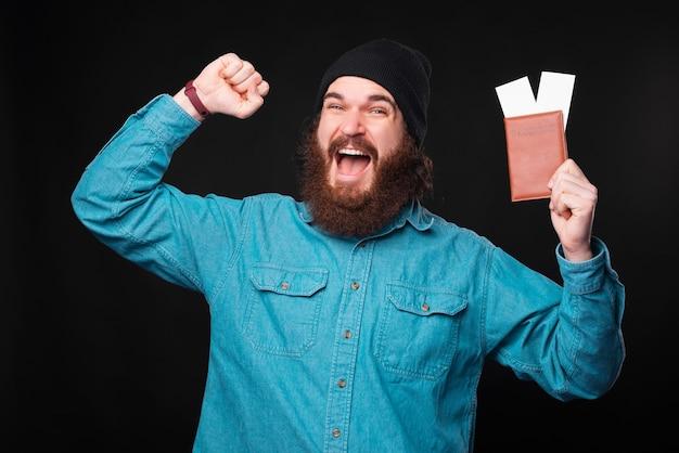 Um jovem hippie barbudo animado está gritando de empolgação para a câmera segurando um passaporte com dois bilhetes de avião perto de uma parede preta