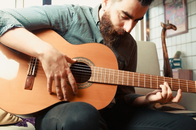 Um jovem hippie com barba e homem de camisa tocando o guittar espanhol no sofá durante um dia ensolarado