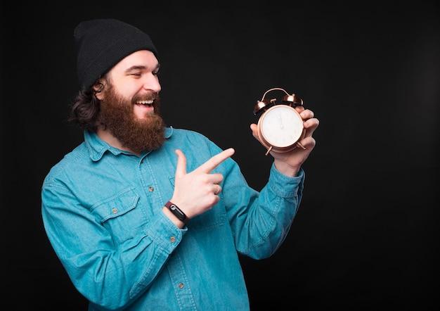 Um jovem hippie feliz está segurando um pequeno relógio e apontando para ele está sorrindo, mostrando que está satisfeito com ele