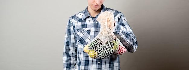 Um jovem hippie masculino contra a parede colorida carregue a sacola ecológica com frutas frescas, sacola ecológica de tecido de algodão