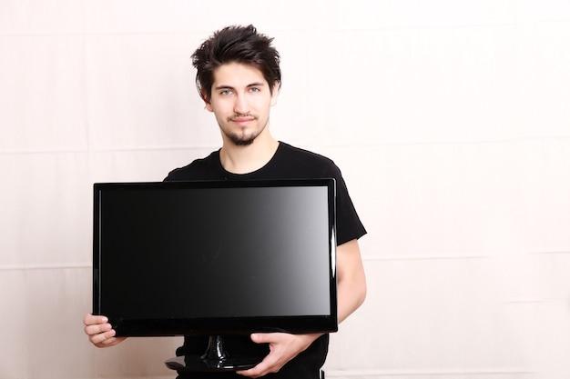 Um jovem hispânico segurando uma tv de tela plana.