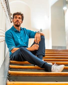 Um jovem homem caucasiano sentado em uma escada em uma jaqueta jeans