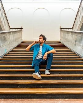 Um jovem homem caucasiano sentado nas escadas em uma camiseta branca e jaqueta jeans
