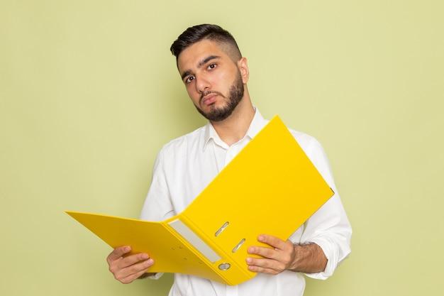 Um jovem homem de camisa branca segurando arquivos amarelos