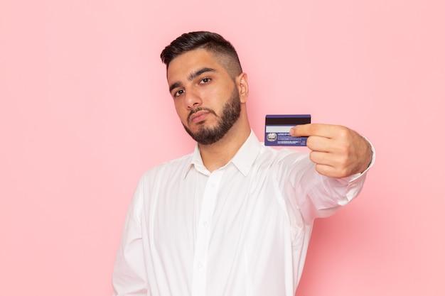 Um jovem homem de camisa branca segurando um cartão de vista frontal