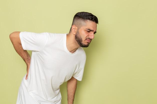 Um jovem homem de camiseta branca com forte dor nas costas, vista frontal