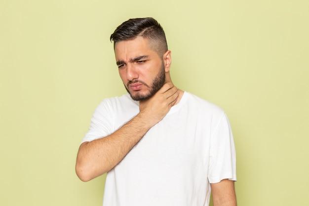 Um jovem homem de camiseta branca com problemas na garganta, vista frontal