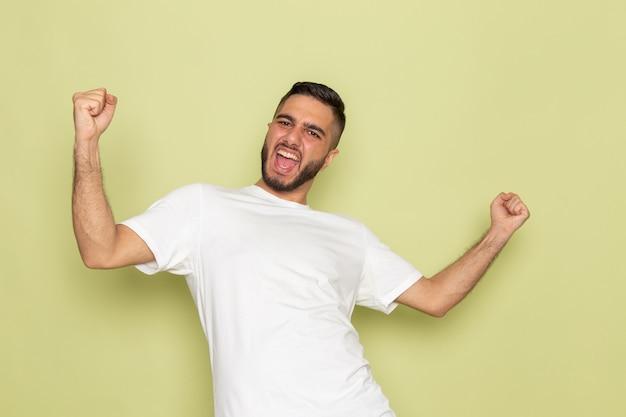 Um jovem homem de frente para uma camiseta branca com uma expressão encantada