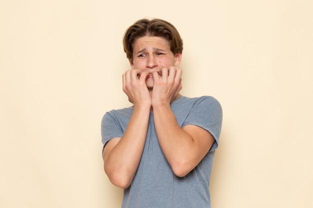 Um jovem homem de frente para uma camiseta cinza com expressão de medo