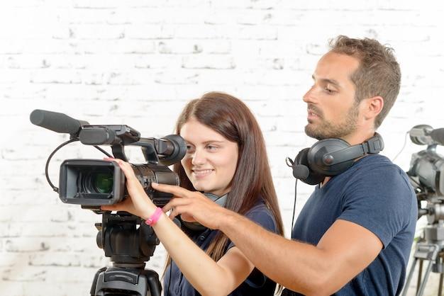 Um jovem homem e mulher com câmera de vídeo profissional