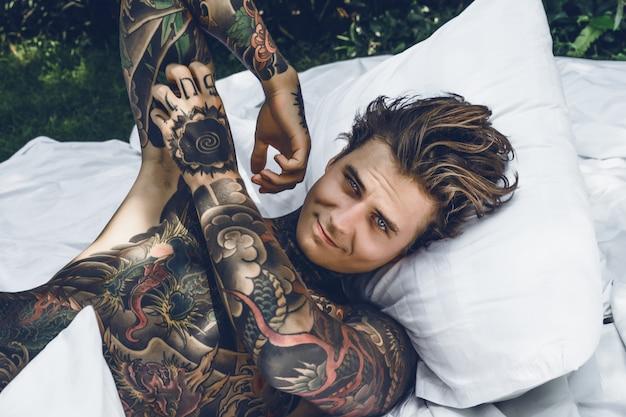 Um jovem homem tatuado bonito de manhã na cama joga até os travesseiros