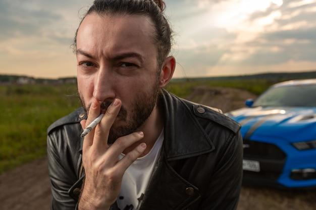 Um jovem interessante com cabelo comprido e barba olha e fuma um cigarro em um campo contra com o pôr do sol.