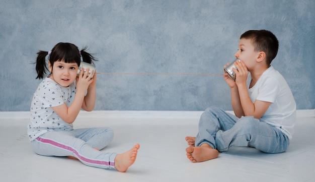 Um jovem irmão e irmã estão conversando com um telefone de lata contra uma parede cinza.