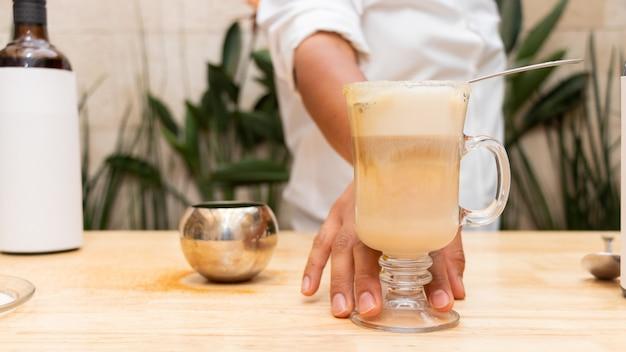 Um jovem irreconhecível exibindo uma bebida preparada em um copo de vidro fosco