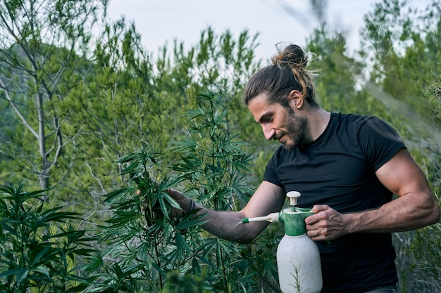 Um jovem jardineiro cuidando de seu jardim verde, fertilizando-o Foto Premium