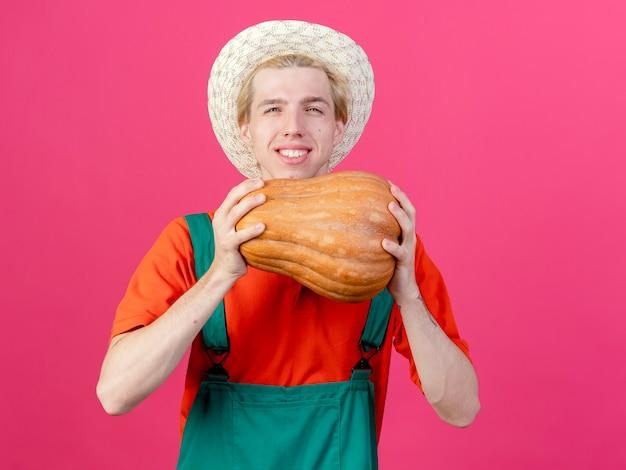 Um jovem jardineiro feliz vestindo macacão e chapéu segurando uma abóbora e sorrindo alegremente
