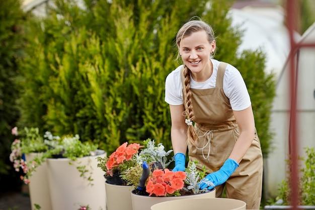Um jovem jardineiro feminino bonito transplanta flores em grandes vasos de cerâmica no jardim.