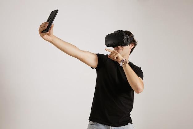Um jovem jogador em uma camiseta preta e fone de ouvido vr posando para uma selfie em seu smartphone na parede branca