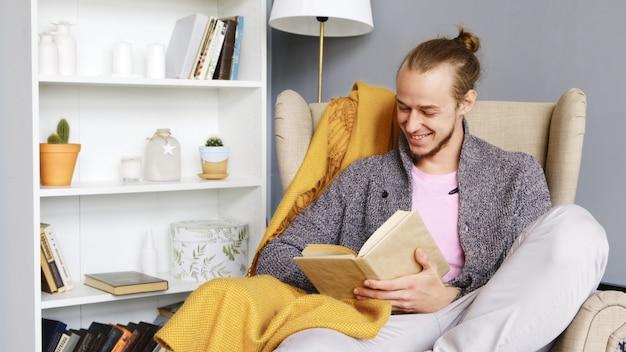 Um jovem lê um livro em um interior acolhedor.