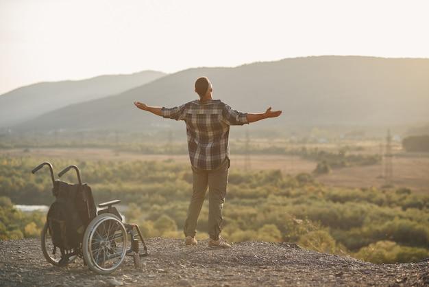 Um jovem levantou-se de uma cadeira de rodas no topo de uma montanha ao amanhecer