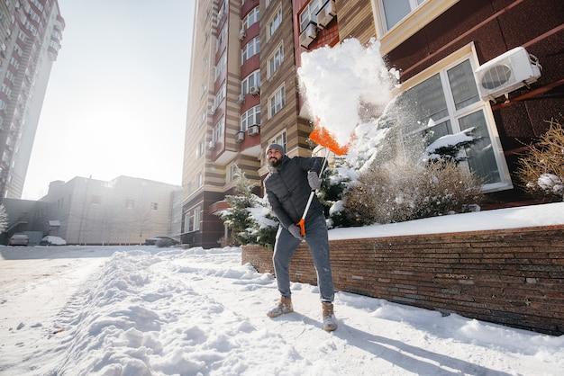 Um jovem limpa a neve na frente da casa em um dia ensolarado e gelado. limpando a rua da neve.