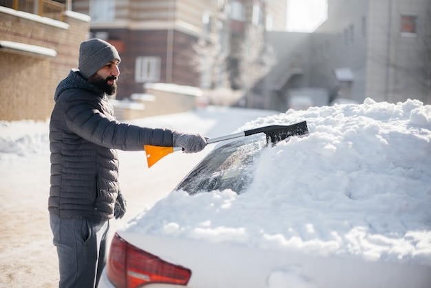 Um jovem limpa seu carro após uma nevasca em um dia ensolarado e gelado.