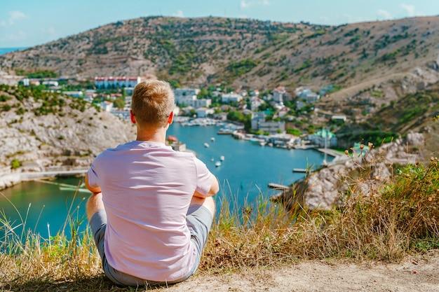 Um jovem loiro aprecia uma paisagem pitoresca com iates e vista para balaclava