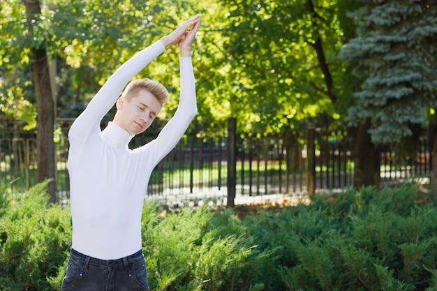 Um jovem loiro de olhos fechados, vestido com um suéter branco e calça jeans preta, levanta as mãos, segurando-as contra o pano de fundo de um parque da cidade. conceito de esportes.