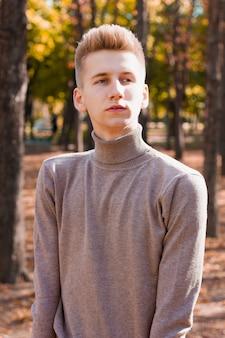 Um jovem loiro, vestido com um suéter bege e calça jeans preta, posando no cenário de um parque da cidade no outono. conceito de foto.